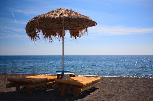 Volcanic beach. Two sun beds on volcanic black sand beach in Greece.