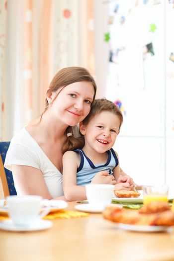 Young happy mother and son having breakfast together