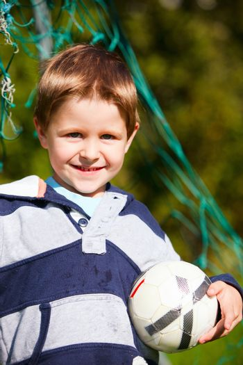 Lifestyle portrait of 4 years old boy with soccer ball