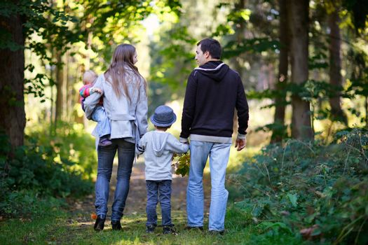 Young family with two kids enjoying beautiful autumn day