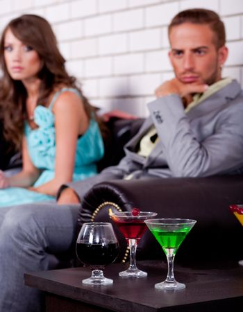 Annoyed young couple in the backround in bar or night club with colorful drinks in focus.