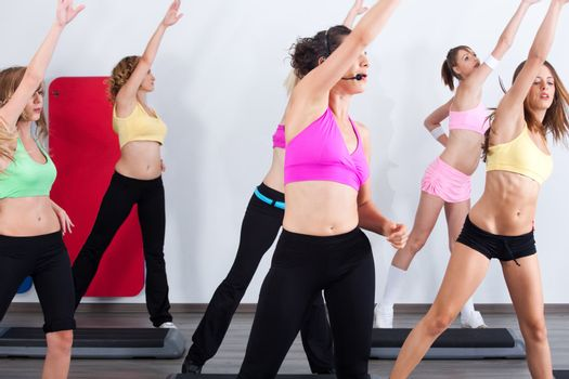 Group of gym people in an aerobics class maintaining fitness...