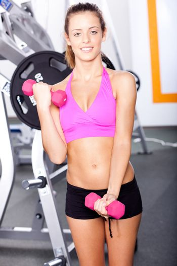 Beautiful sporty woman with a dumbbell in the gym.