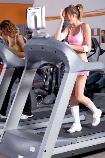 Woman on running machine in gym with her friend..