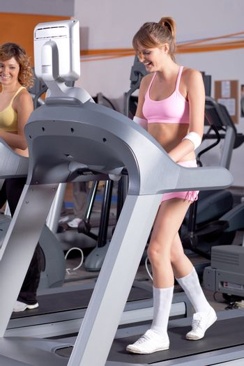 Woman on running machine in gym with her friend.