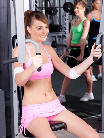 Portrait of young female exercising in gym...