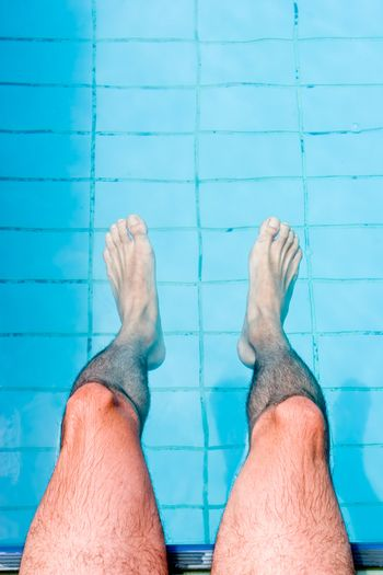 Male legs on water, by the pool.