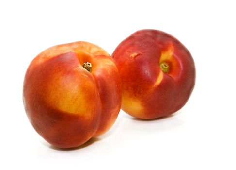 A pair of luscious sunripened nectarines on a white background