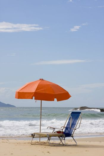 Two chairs and a parasol on a sunny beach