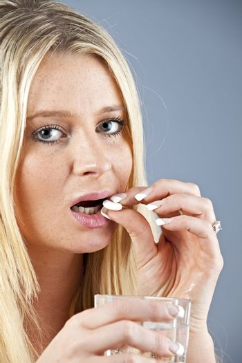 blonde woman taking a pill with a glass of water