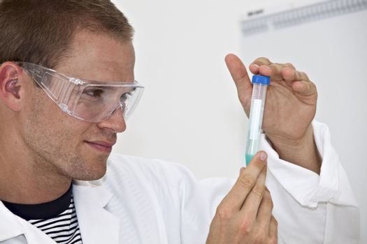 young lab technician looking a at medical sample