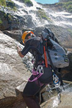 Men descending in rappeling a waterfall