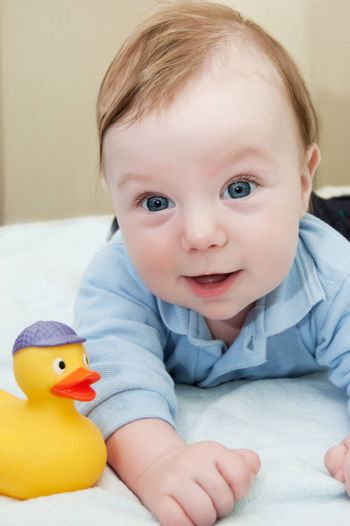 Smiling baby boy and duck toy