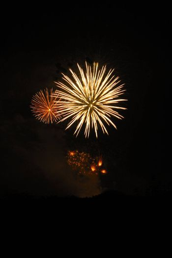 Two firework bursts in the night sky, with others just exploding beneath them. A faint hint of the horizon below. Space for text in the dark of the night sky.