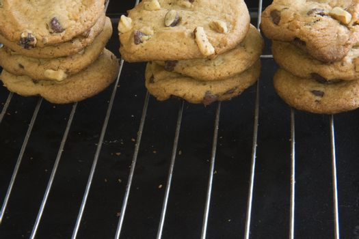 cooling racks and three stacks of cookies with choclate chips and walnut, crumbs