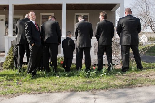 The groomsmen and other male members of a bridal party peeing in the bushes while the groom laughs.