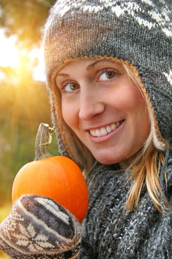 Young woman holding a pumpkin on an autumn day