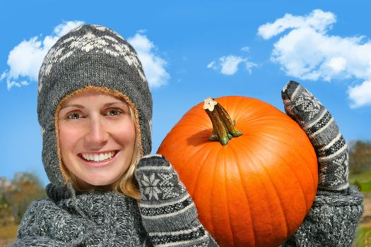 Young woman holding up a big pumpkin against a blue sky