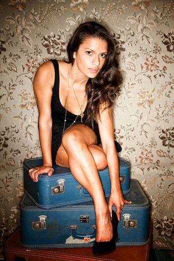 Woman sitting on suitcases adjusting her shoe