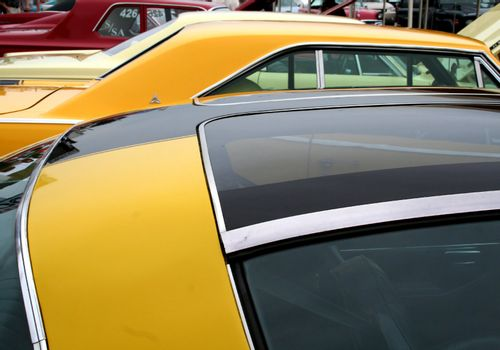 colorful classic muscle cars in parking lot