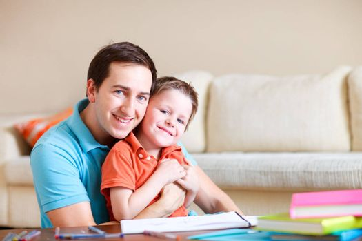 Young father and his son drawing and reading together