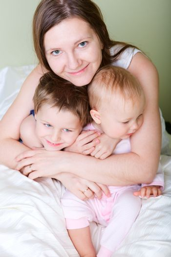 Happy young mother with her son and daughter in bedroom