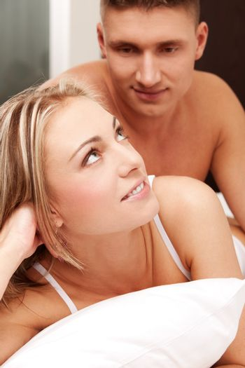 Young smiling couple in a bed on white sheets