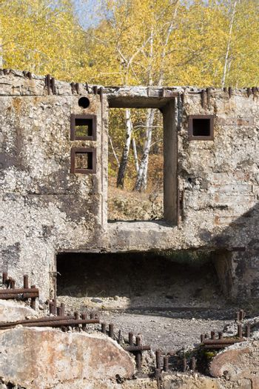 Damaged concrete building against of autumn trees