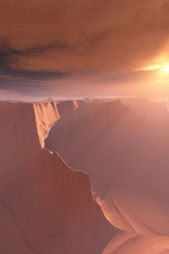 Sunrays shine down on this canyon landscape.