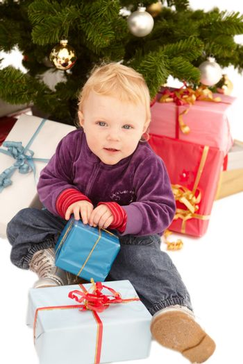 Cute little girl opening christmas gifts