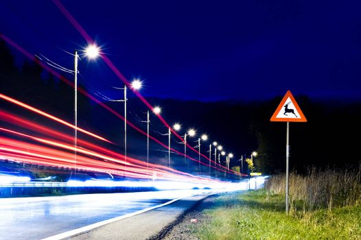 Danger sign by the road at night with cars passing by