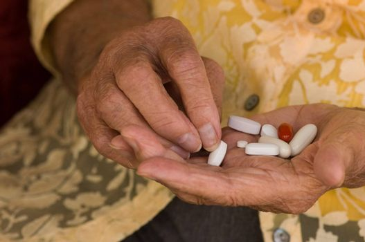 senior hand sorting through a handful of medications