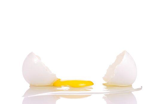 Fresh broken egg with yolk on white background
