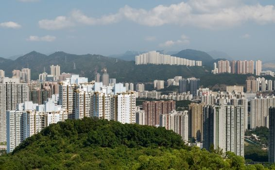 Tall apartments with green mountain and blue sky