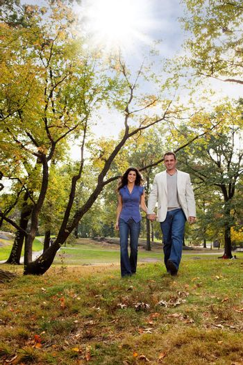 A happy couple walking in the park - looking at the camera