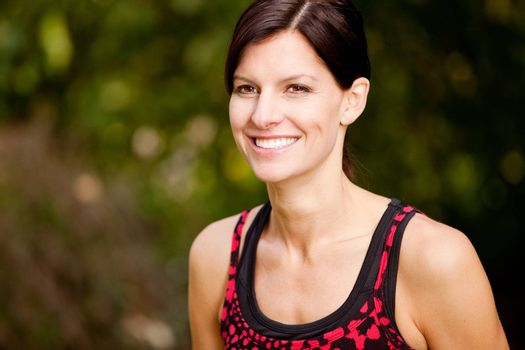 A happy fitness woman in the park - lifestyle portrait