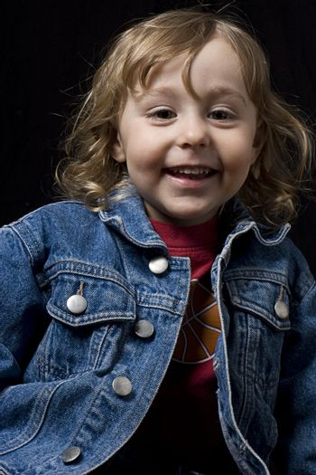 Portrait of a two year old boy wearing a jean jacket with great big smile