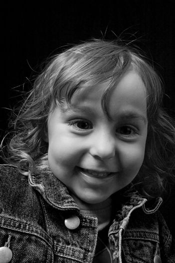 black and white portrait of a two year old boy wearing a jean jacket with great big smile