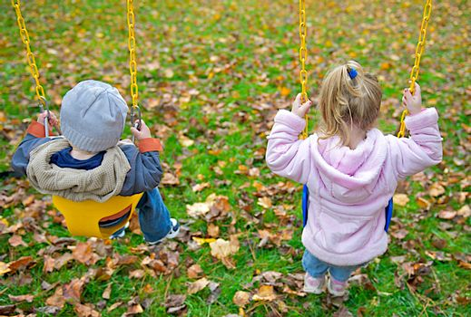 Two young children sitting in swings.