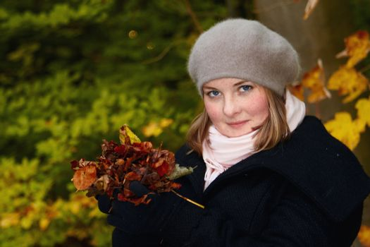 Autumn - Cute young woman holding leaves