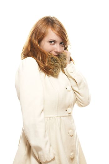 young redhead woman covering her face in fawn winter coat