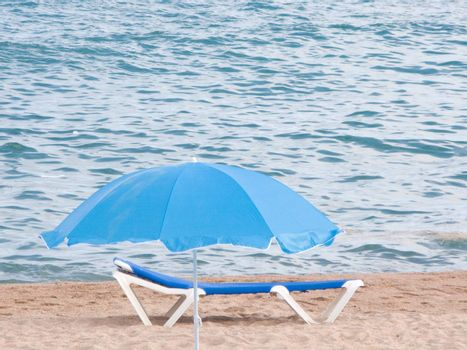 Blue umbrella an chair for relax in the beach
