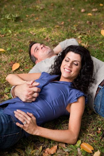 A man and woman relaxing in the park laying in the grass and dreaming - focus on the woman