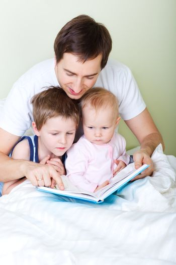 Young father and two kids reading book in bed