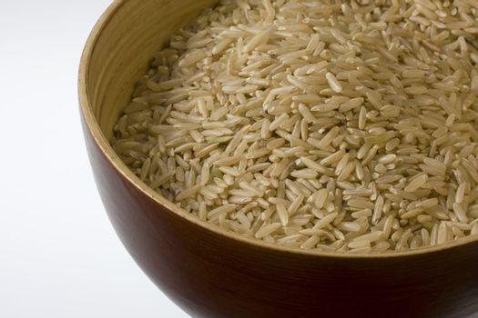 a wooden bowl of long grained brown rice against white background