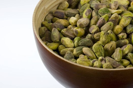 a wooden bowl of shelled pistachio nuts against white background
