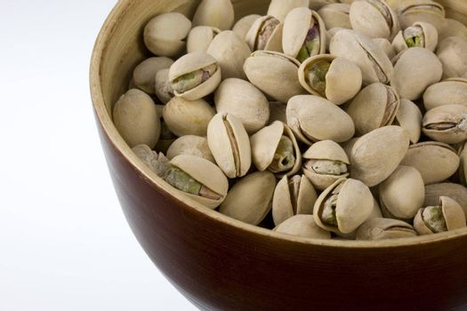 a wooden bowl of salted and roasted pistachio nuts, white copy space