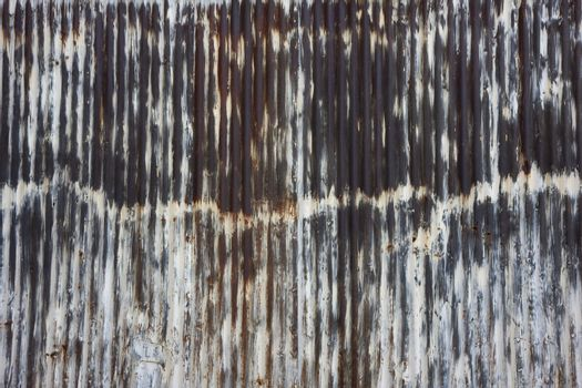 rusty metal wall which used to be painted white