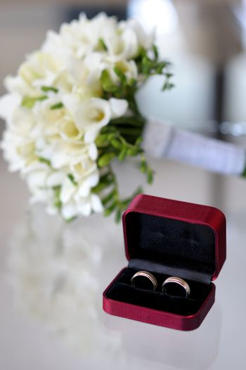 Wedding rings in the nice box and the nice bouquet of flowers