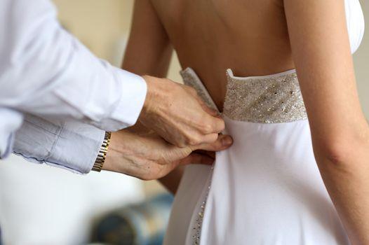 Groom is helping bride to put her nice wedding dress on